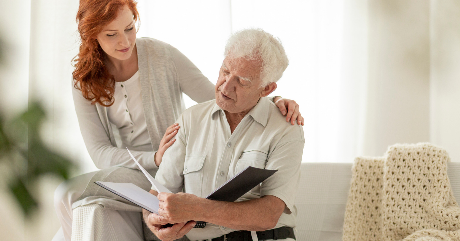 Older man looking at paper with woman
