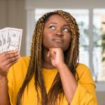Woman thinking while holding money.