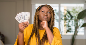 Woman thinking while holding money.
